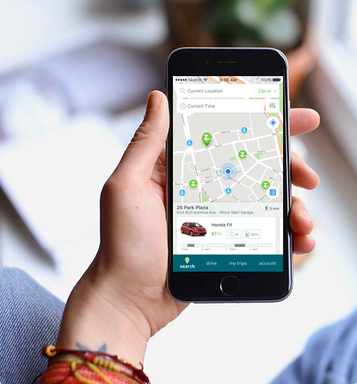A hand holding a cell phone with a map of Zipcars on the screen