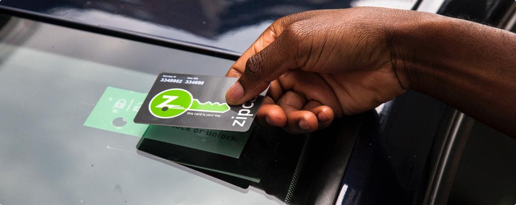 A hand holding a Zipcard to a windshield sensor